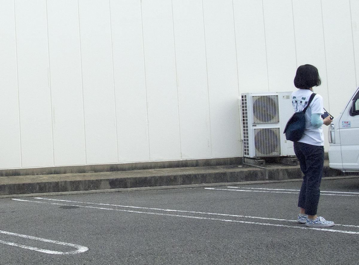 大きな壁が印象深い駐車場で作品を待つ郷さん